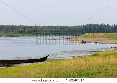 Beautiful rural landscape with river and wooden boats