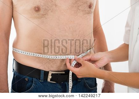 Close-up Of A Doctor Measuring Person's Waist With Measuring Tape