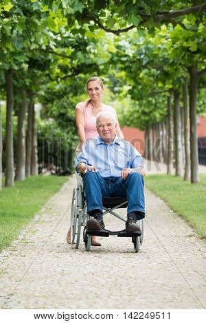 Happy Young Woman With Her Old Senior Father On Wheelchair In Park