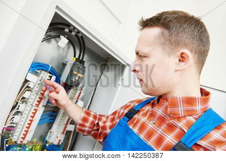 electrician works with electric meter tester in fuse box