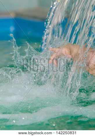 Hand of child creates splashes in the water flow