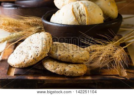 Wholemeal bread whish flax linen seeds in clay bowl and wheat spike on wooden board