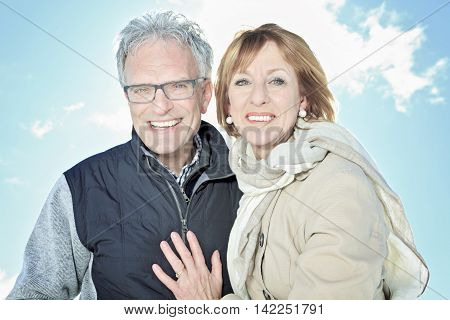 A Portrait of happy senior couple in winter season with sky on the background.