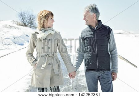 A Portrait of happy senior couple in winter season hand on hand.