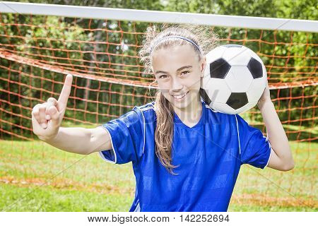 A Youth Soccer player play soccer in a beautiful day
