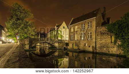 Romantic nocturnal view of a canal in Bruges. Buildings trees and the bridge are reflected in the water