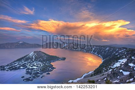 Sunset at Crater Lake with red clouds reflection in lake.