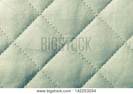 Abstract green soft textured background with squares. Quilted textile tiled texture