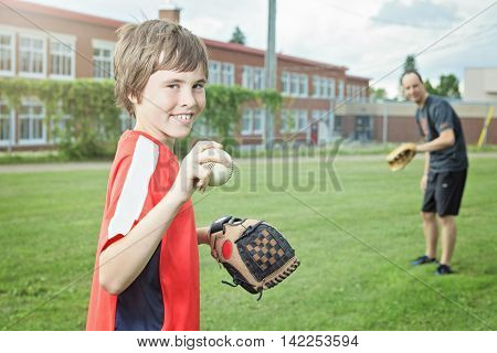 A Portrait of a father and son play baseball in a field