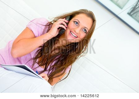 Smiling attractive woman sitting on sofa and talking on phone