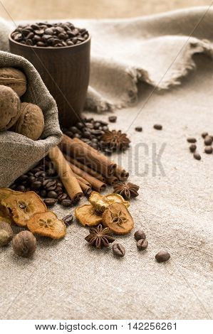Coffee beans in a clay cup, next to nuts and dried fruits