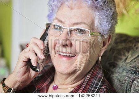 A Portrait of a happy senior woman at home talking on the phone.