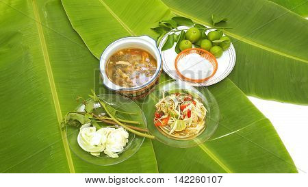 Papaya Slad and Spicy Pork Soup Thai Isan favorite herbal green food for diet control have eat with noodles vegetable lemon cabbageThai morning glory all on banana leaf.