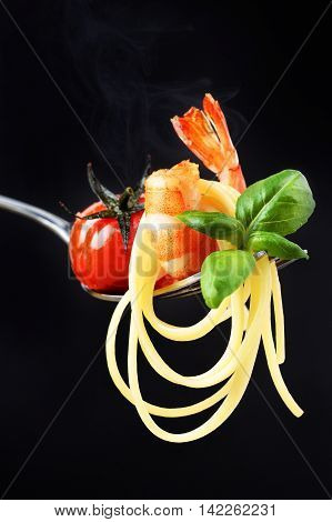 Linguini served with grilled cherry tomato shrimp and basil on fork with smoke
