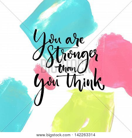 You are stronger than you think. Motivational saying at artistic paint strokes background.