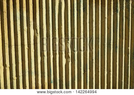 Yellow wall with vertical ribbed surface, under the sunlight.
