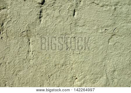 The old plastered wall cracked of yellow green paint.