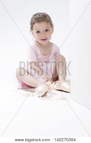 Smiling Positive Caucasian Ballerina Trying On Miniature Pointes. Posing Against White Background. Vertical Image Orientation