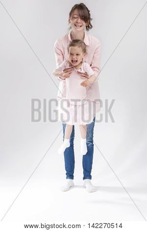 Mother and Little Daughter Together Having Fun and Hugging. Posing Against White. Vertical Image Composition