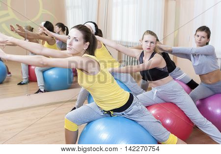 Sport Concepts. Group of Five Female Sportswomen Having Hand Stretching Exercises With Fitballs In Class. Horizontal Image