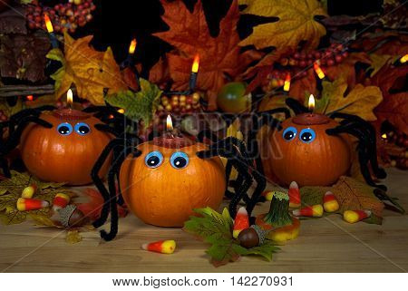 Halloween pumpkin spider candles with candy corn and fall leaves.