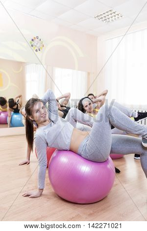 Sport Concepts. Group of Five Laughing Smiling Caucasian Females Having Muscles Stretching Exercises in Class. Vertical Image Composition