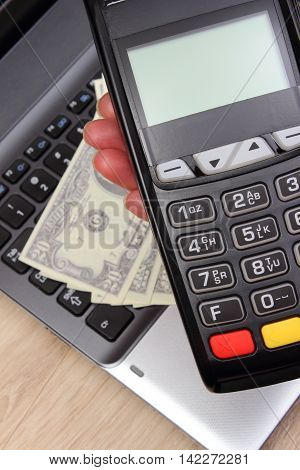 Hand Of Woman Using Payment Terminal, Currencies Dollar On Laptop In Background