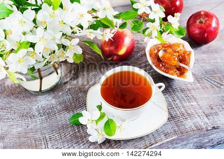 Cup of tea on wooden table and apple jam. Tea time concept. Breakfast tea cup served with flowers.