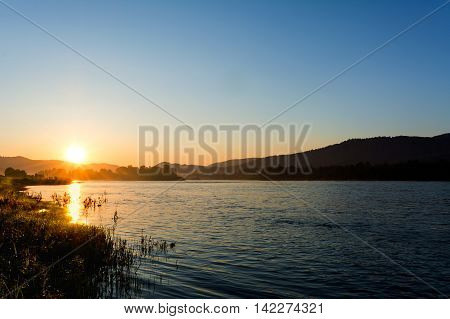 Summer sunrise over beautiful river landscape. Lake landscape. Beautiful landscape with golden sunset.