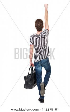 Back view of  man with bag.  Raised his fist up in victory sign.  Rear view people collection.  backside view of person.  Isolated over white background. Curly boy in a striped vest holding a bag in