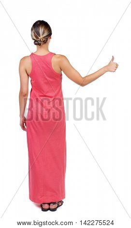 Back view of  woman thumbs up. Rear view people collection. backside view of person. Isolated over white background. A slender woman in a long red dress shows thumb up.