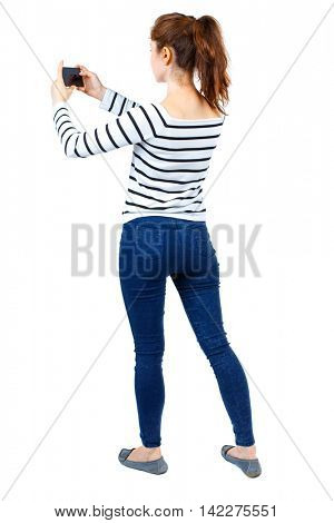 back view of standing young beautiful  woman  using a mobile phone. girl  watching. Rear view people collection.  backside view of person.  Isolated over white background. Girl in a striped sweater