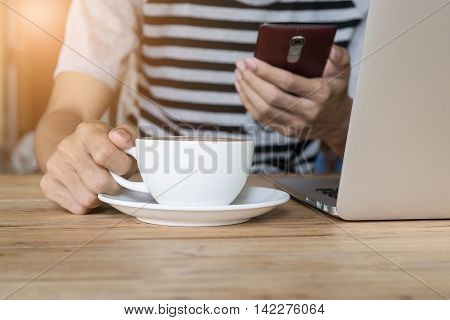 young man working at coffee shop using smart phone and laptop computer man's hands using smart phone in interior man at his workplace using technology flare light