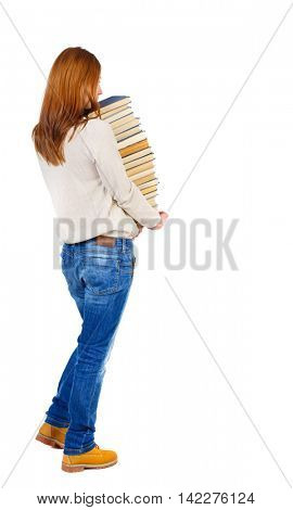 Girl carries a heavy pile of books. back view.  Rear view people collection.  backside view of person.  Isolated over white background.  Blonde in brown shoes holds a lot of textbooks.