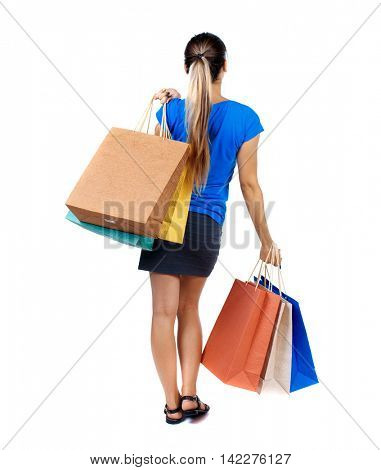 back view of woman with shopping bags. backside view of person.  Rear view people collection. Isolated over white background. girl in a short skirt and a blue T-shirt slung over his shoulder shopping