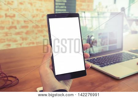 Close up of a women using smart phone with blank mobile and cup of coffee .Smart phone with blank screen and can be add your texts or others on smart phone.