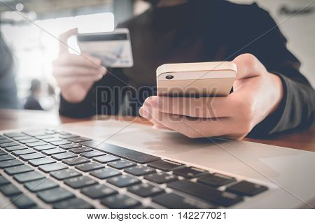 Online paymentWomen's hands holding a credit card and using smart phone for online shopping