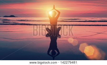 Silhouette yoga woman in Lotus pose on beach during sunset. With the reflection in the water. Harmony and meditation.