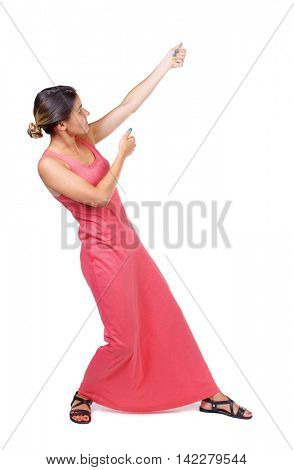 back view of standing girl pulling a rope from the top or cling to something. girl  watching. Rear view people collection.  backside view of person.  Isolated over white background. A slender woman in
