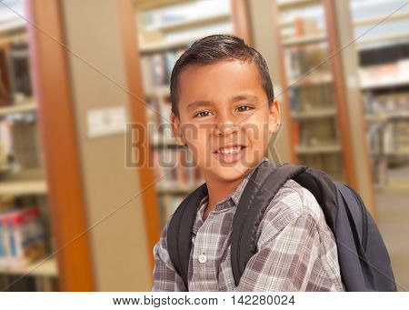 Happy Hispanic Student Boy with Backpack in the Library.