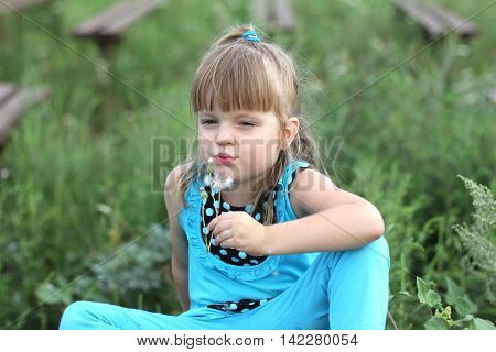 little girl with long hair playing on green grass in summer