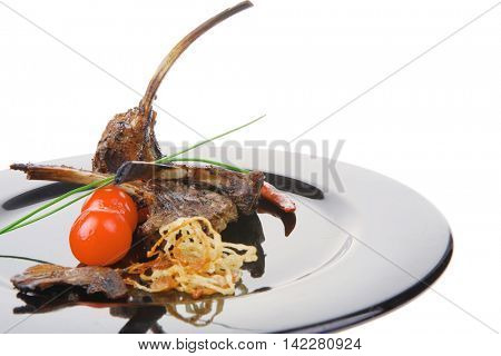 roast ribs on plate with tomatoes and chives
