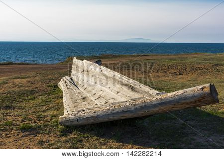 In the village Gremyachinsk on the sandy shore of lake Baikal, lies the old fishing boat, which was quite rotted and collapsed.