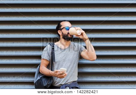 leisure, technology, communication and people concept - man with smartphone drinking coffee from disposable paper cup on city street