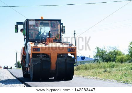 HALBSTADT, RUSSIAN FEDERATION - AUGUST 8, 2016: Road-roller paving new asphalt in the countryside
