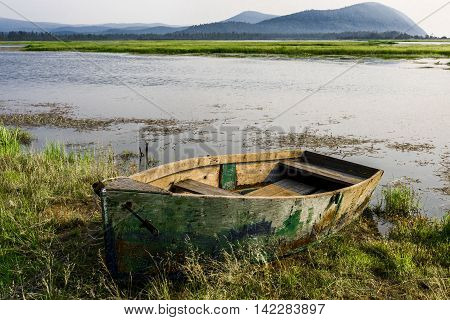 Old fishing boat, beautifully looks on the grassy Bank of the river, especially in the setting sun.