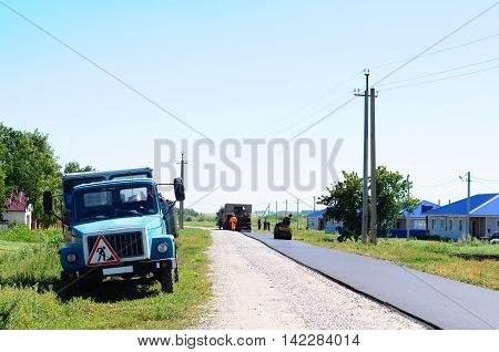 HALBSTADT, RUSSIAN FEDERATION - AUGUST 8, 2016: Constructing new asphalt in the village with transport