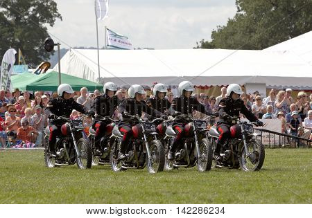 WEEDON, UK - AUGUST 29: Members of the Royal Signals White Helmet motorcycle display team perform a series of stunts for the public at the Bucks County show on August 29, 2013 in Weedon.