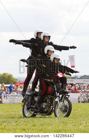 WEEDON, UK - AUGUST 29: Riders of the Royal Signals White Helmets display team demonstrate formation riding on a single motorcycle for the public at the Bucks County show on August 29, 2013 in Weedon