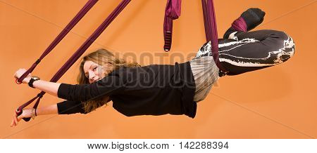 Woman making aerial yoga exercises indoor fly yoga